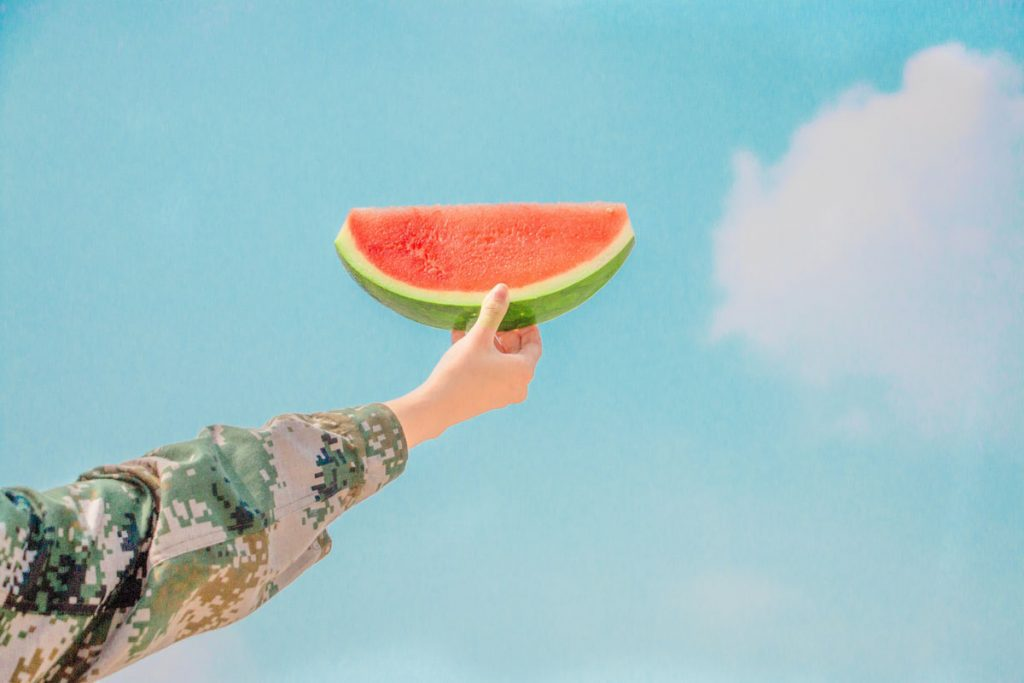 female arm holding watermelon slice to the sky
